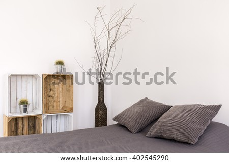 Light bedroom with large bed, handmade wooden regale and decoration in vase