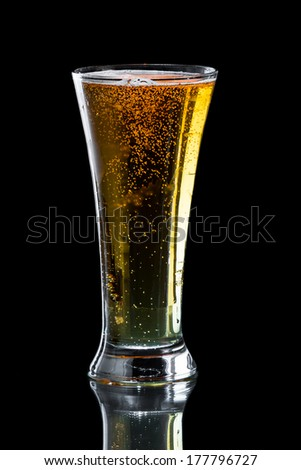 light beer isolated on a black background served in a chill tall glass
