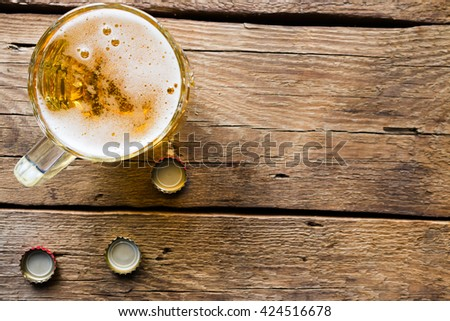 light beer mug on the wooden background - stock photo