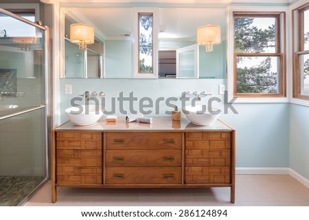 Light blue Bathroom Interior with Magnificent Wooden Vanity Furniture, Double White Porcelain Bowl Washbasin, Wall Mounted Mirror and Glass shower. - stock photo