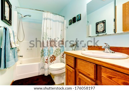 Light blue bathroom with wood cabinets. tile floor. Decorated with blue and white towels and curtains