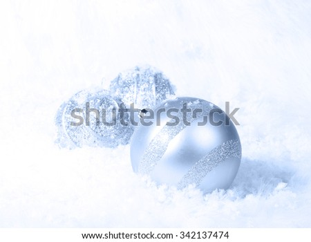 Light blue Christmas ornaments in a bed of white snow. Selective focus on band of glitter on large ornament. - stock photo