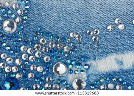Light-blue denim with blue and silver rhinestones, background - stock photo