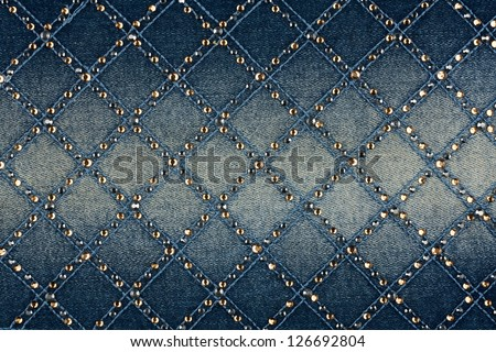 Light-blue denim with yellow and silver rhinestones, background - stock photo