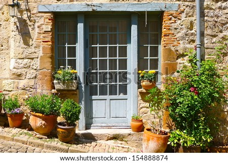 Light blue door with paned windows in an old stone house with potted plants in front in a village in rural southern france. - stock photo