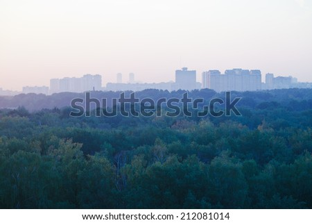 light blue early sunrise over urban houses and park in summer morning - stock photo