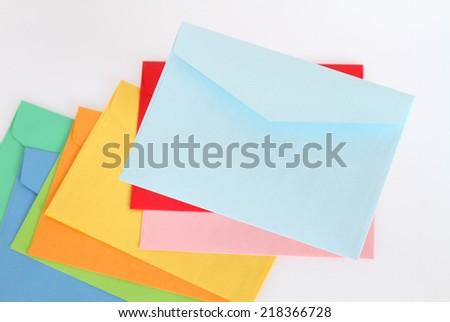 Light blue envelope on the colorful envelopes - stock photo
