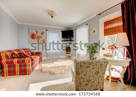 Light blue family room with comfortable red sofa, floral chair, wooden white table and white soft bear rug
