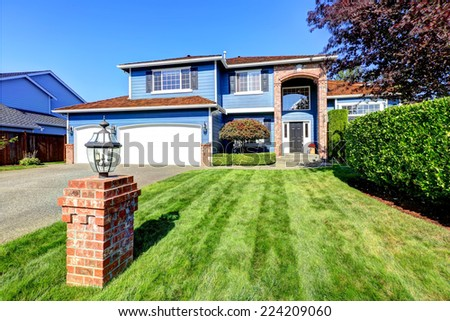 Light blue house exterior with brick trim and tile roof. Garage with driveway and front yard landscape with lawn and trimmed hedges - stock photo