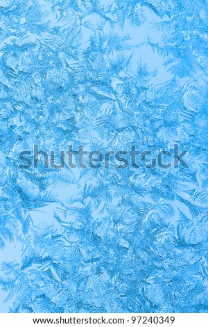 Light blue Ice flower frosting on a window. See my portfolio for more - stock photo