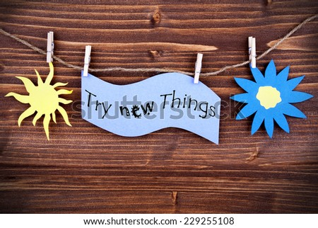 Light Blue Lable Saying Try New Things On Wooden Background Hanging On A Line, One Blue Flower Symbol And One Yellow Sun Symbol Background Is Old Fashion - stock photo
