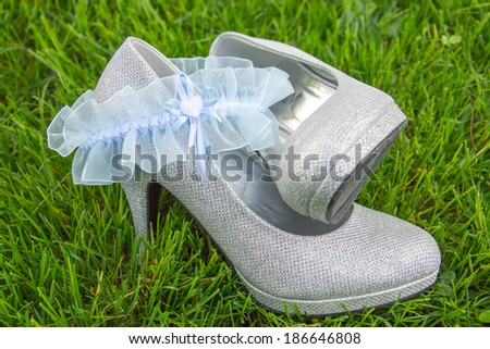 Light blue lace garter arranged with silver high heel shoes sitting in grass - stock photo