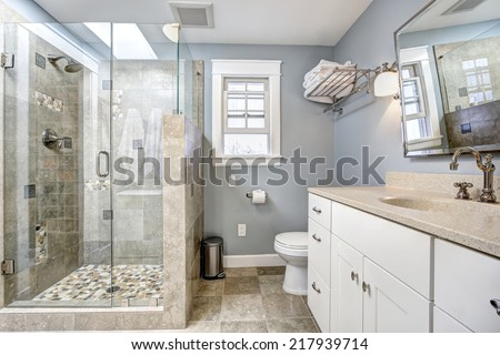 Light blue modern bathroom interior with glass door shower and white cabinet with  mirror - stock photo
