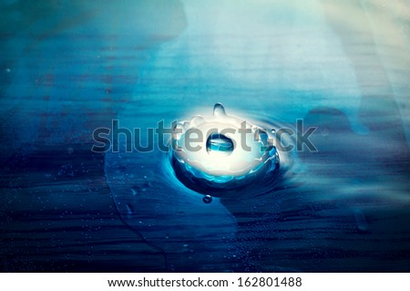 Light blue planet droping into the water  - stock photo