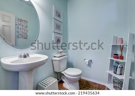 Light blue restroom with white washbasin stand. Wooden shelf in the corner with towel baskets and candle