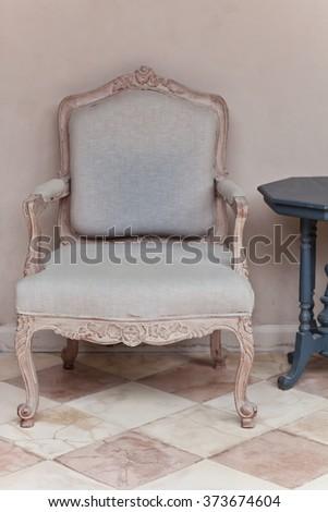 Light Blue Vintage Luxury Armchair in Interior near beige Wall - stock photo