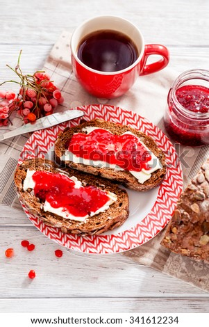 light breakfast or lunch , sandwiches of rye bread with butter , raspberry jam , berries and black tea on the background of the village - stock photo