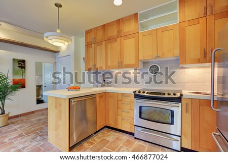 Light brown kitchen interior with steel appliances and tile back splash trim in apartment house. Northwest, USA