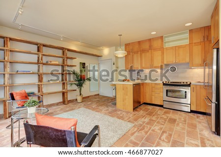 Light brown kitchen interior with steel appliances. View of sitting area with long book shelves. Northwest, USA