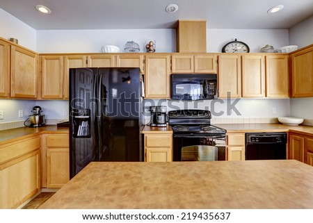 Light brown kitchen room with island and black appliances