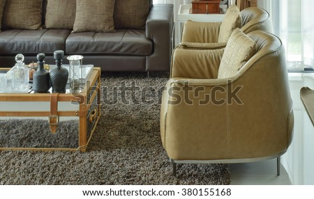 light brown leather armchairs and dark brown leather sofa in the living room with area rug