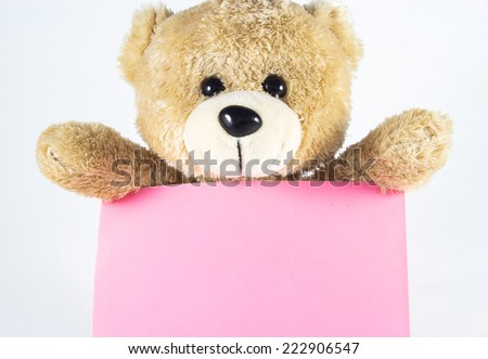 light brown teddy bear holding pink paper