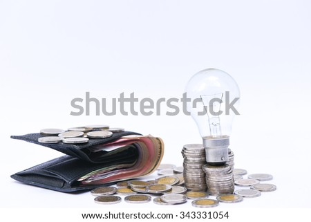 light bulb and money with copy space on white background - saving energy concept - stock photo