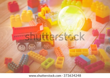 light bulb and truck toy with colorful block toy.jpg - stock photo