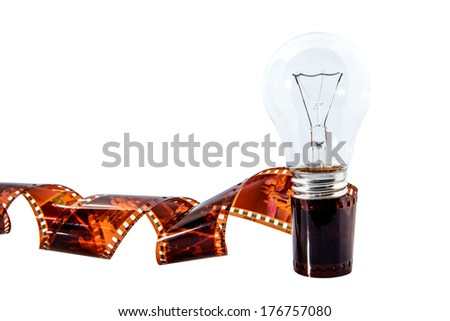 Light bulb and used photography film strip over white background - stock photo