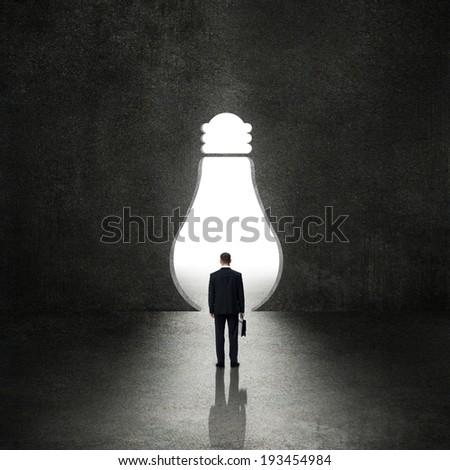 Light bulb before the businessman - idea concept - stock photo
