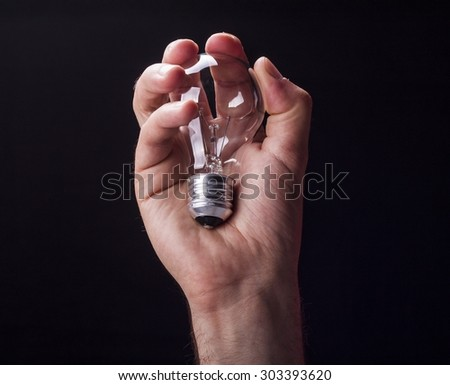 light bulb hold in hand on black background
