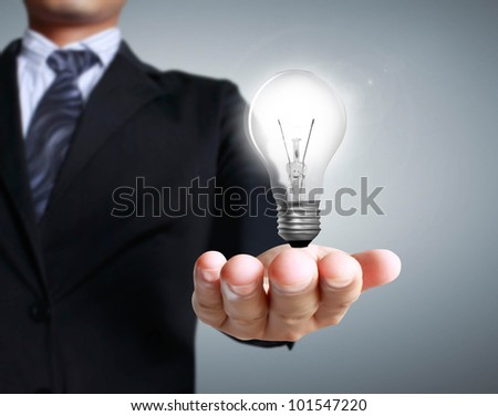 Light bulb in a hand on a gray background - stock photo