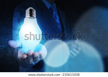 Light bulb in  businessman hand on blue tone as concept - stock photo
