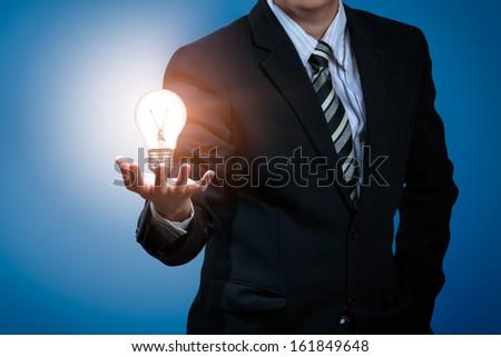 Light bulb in businessman's hand - stock photo