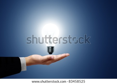 Light bulb in hand business woman on blue background