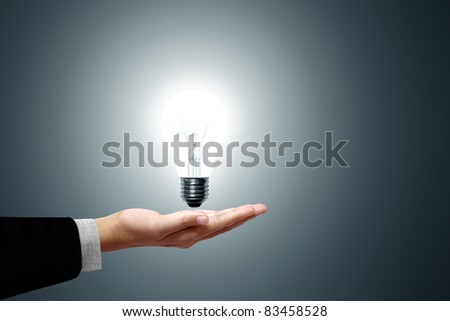 Light bulb in hand business woman on gray background - stock photo
