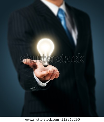 Light bulb in hand businessman - stock photo