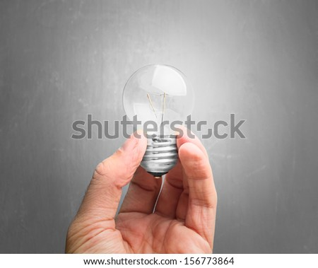 Light bulb in hand on gray background