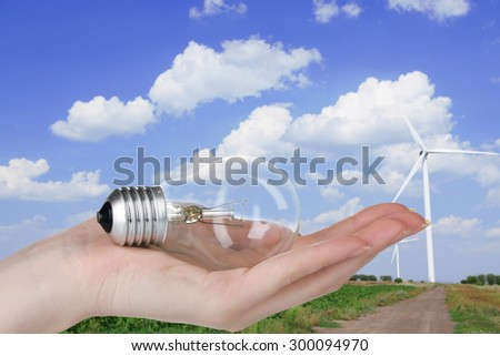 Light bulb in hand on windmills field background - stock photo