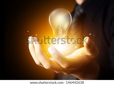 Light bulb in man hand - stock photo