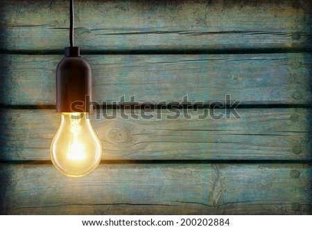 Light bulb lamp on wooden background with copy space - stock photo