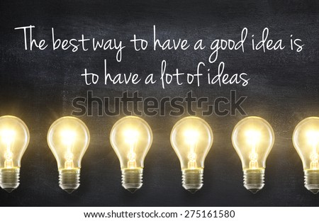Light bulb lamps on blackboard background with idea quote - stock photo