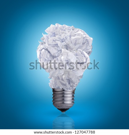 light bulb made of crumpled paper on blue background - stock photo
