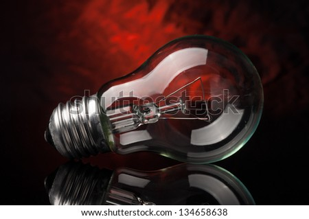 Light bulb on black and red background - stock photo