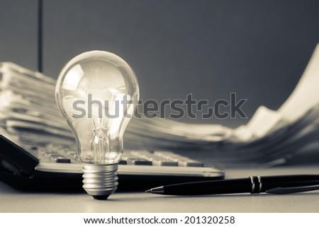 Light bulb on financial desk - stock photo