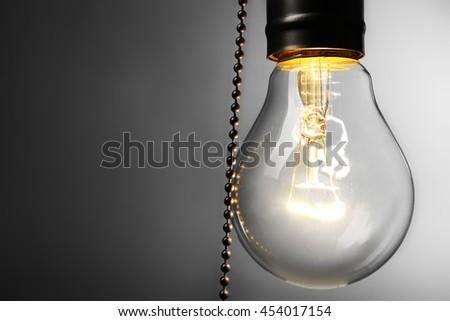 Light bulb on grey background - stock photo