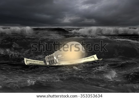 Light bulb on money boat in dark stormy sea with wave coming. - stock photo