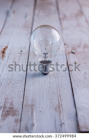 light bulb on old wooden floor - stock photo