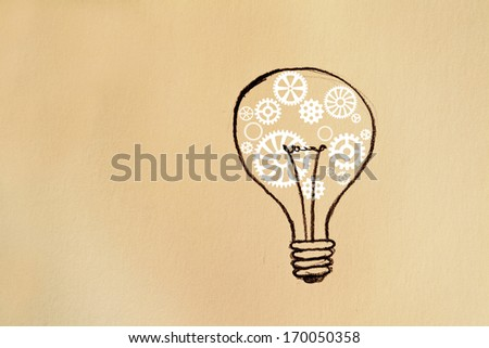 Light bulb on paper background with white gears - stock photo