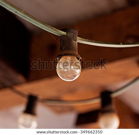Light bulb on the cable against brick wall - stock photo